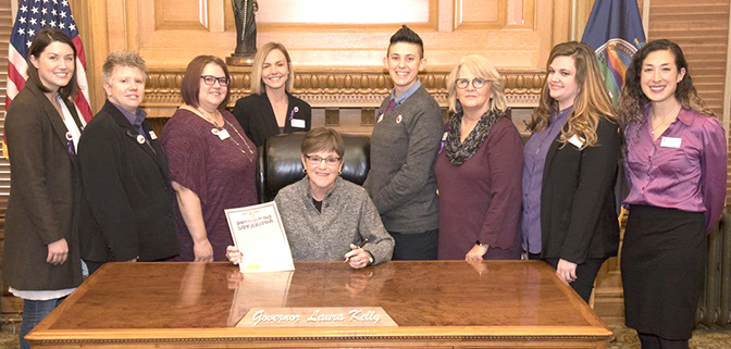 The image shows eight KCSDV staff members and coalition member program staff with Kansas Governor Laura Kelly at the 2019 Domestic Violence Awareness Month Proclamation Signing Ceremony in Topeka. The image is by the Kansas Governor's Office and edited by KCSDV.